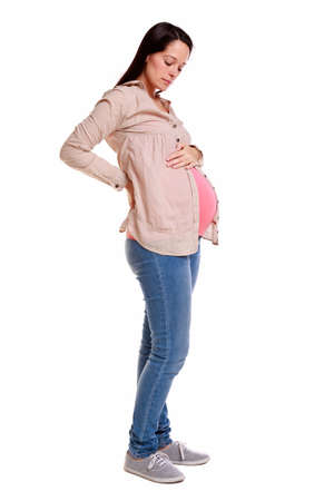 back strain: A pregnant woman with her hands on her back looking down at her bump, isolated on a white background. Stock Photo