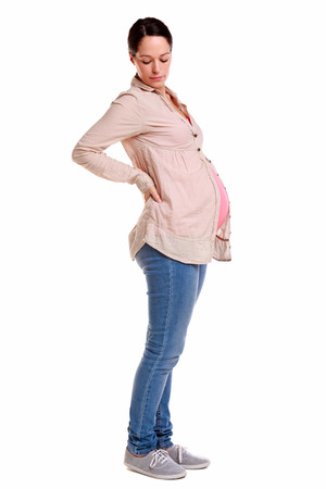 back strain: A pregnant woman with her hands on her back, isolated on a white background. Stock Photo