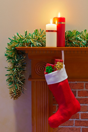 Christmas stocking full of presents hanging on a mantlepiece on Christmas day. photo
