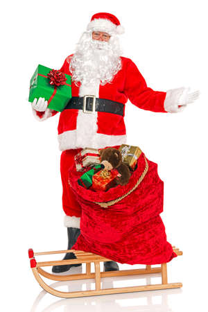 Santa Claus or Father Christmas with a sack full of gift wrapped toys and presents on a sledge, isolated on a white background. photo