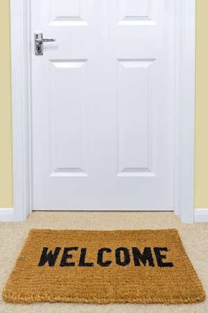 A Welcome doormat in front of a door. Stock Photo