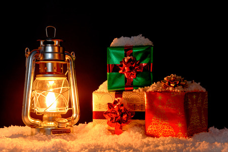 hurricane lamp: Gift wrapped Christmas presents on snow illuminated by the glow from an oil lantern, black background. Stock Photo