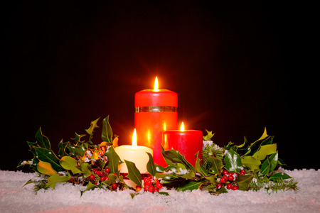 Christmas still life of three candles on snow surrounded by a fresh green holly, ivy and spruce garland against a black background. photo