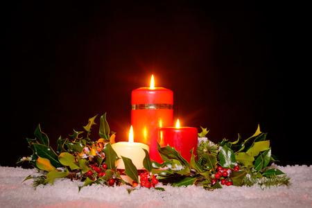 corona de adviento: Navidad sigue la vida de tres velas en la nieve rodeada por un fresco verde acebo, hiedra y abeto guirnalda sobre un fondo negro. Foto de archivo