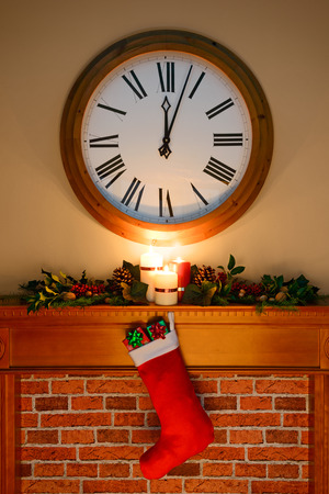 past midnight: Its just past midnight on Christmas Eve  Day and Santa has been, gifts are in the stocking hanging over the fireplace, as candles burn on the mantlepiece surrounded by a holly and ivy garland. Stock Photo