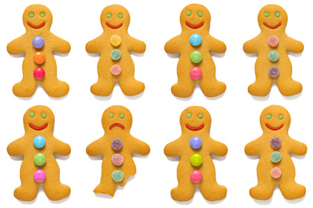 odd one out: Smiling gingerbread men with one exception, isolated on a white background. Stock Photo
