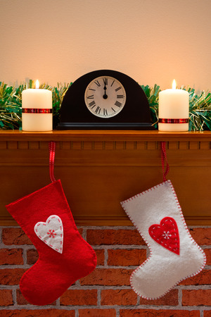 Christmas stockings hanging on a chimney mantlepiece, the clock shows midnight on Christmas Eve. photo