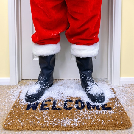 welcome door: Santa standing on a welcome mat shaking off the snow. Stock Photo