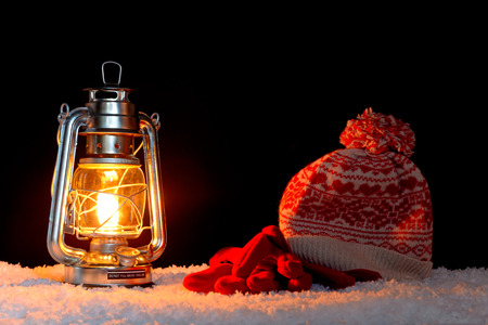 warmth: An oil filled lantern on snow with a bobble hat and gloves, black background.