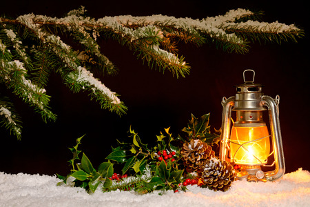 Christmas scene - an oil filled lantern burning bright with snow covered tree, holly and ivy lit up by the glow of the lamp. Stock Photo