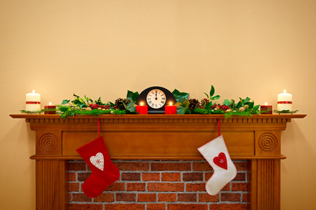 Christmas stockings hanging over the fireplace at midnight on Christmas Eve, the mantlepiece is decorated with festive holly and ivy garland plus candles. Plenty of copy space to add your own message. photo