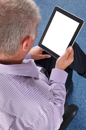 personas leyendo: Hombre de negocios sentado en una oficina con un tablet PC. Trazado de recorte para la pantalla para a�adir su propio mensaje o imagen.