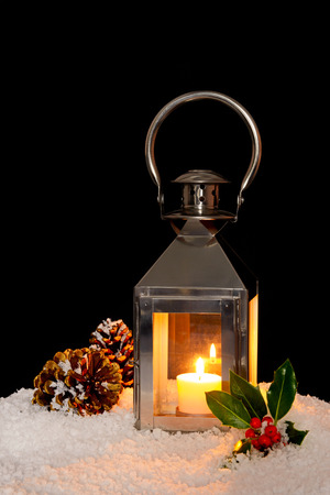 A Christmas lantern with a candle burning in snow with holly and pine cones, black background.