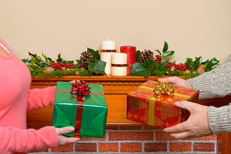 A couple at home exchanging Christmas gifts with a decorated mantlepiece in the background. Stock Photo