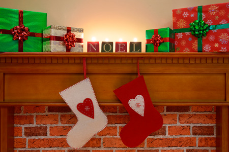 fire surround: Christmas stockings hanging over the fireplace with gift wrapped presents and NOEL candles on the mantlepiece, lit up by the glow of the fire. Stock Photo
