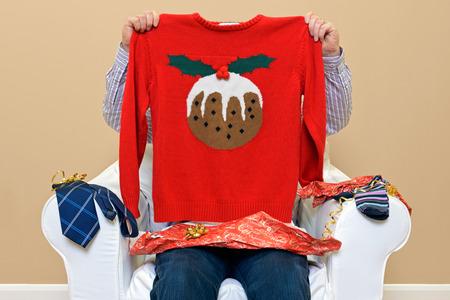 maglioni: Un uomo che apre i regali di Natale per scoprire ha ottenuto un ponticello a tema natalizio di andare avanti con le calze normali e cravatta.