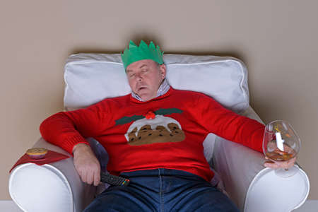jumpers: A Christmas tradition - Dad has fallen asleep in an armchair after dinner in front of the TV, hes wearing the jumper he got for Christmas and is about to drop a glass of brandy.