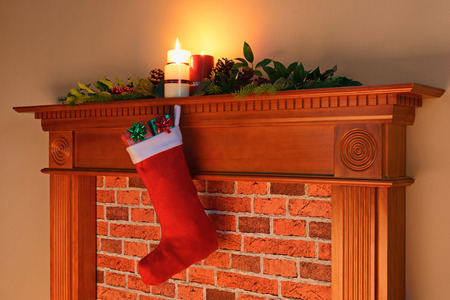 mantelpiece: A Christmas stocking full of gifts hanging from a mantelpiece lit by the glow from the fireplace on Christmas Day.