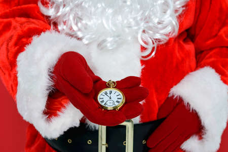 santa outfit: Santa Claus or Father Christmas checking his gold pocket watch to see if its time for Christmas. Stock Photo