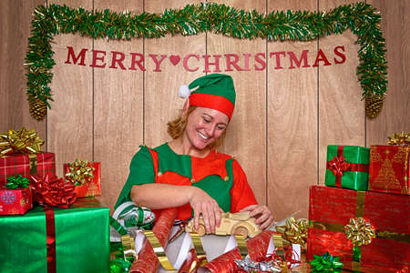 An elf wrapping Christmas presents in Santas workshop at the North Pole