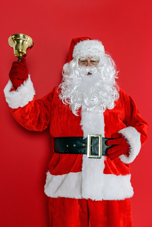 Santa Claus or Father Christmas ringing his bell against a red background. photo