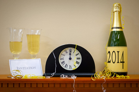 A clock showing midnight at New Year with a bottle of champagne labelled 2014, glasses and invitation surrounded by streamers. photo
