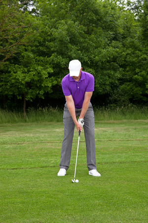 follow through: Male golfer playing a mid iron shot from the edge of the fairway, series of four images from addressing the ball to the follow through.
