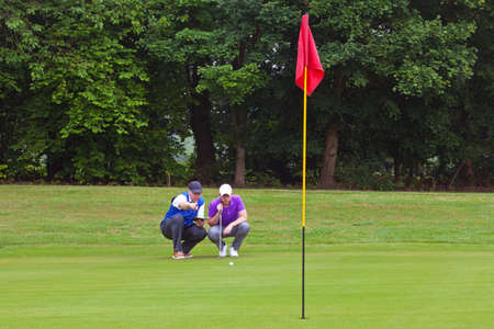 caddie: A professional golfer and his caddy reading the green to judge the line of the putt. Series of three photos. Stock Photo