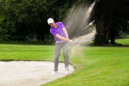A professional golfer hitting his ball out of a bunker with the sand and ball in mid-air.