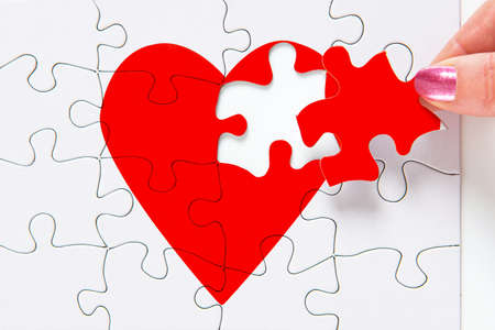missing: A woman putting the missing piece of a jigsaw red heart in place, good image to represent a love, broken heart, heartbreak, romance or Valentines theme.