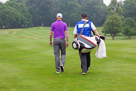 caddie: Golfer and caddy walking towards a ball on a par 4 fairway.