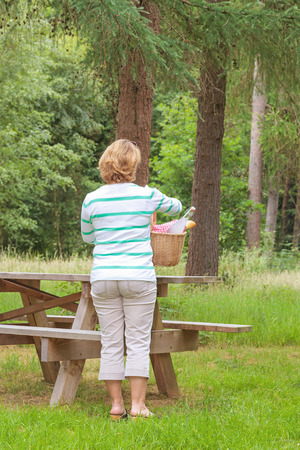 alfresco: Rear view of a woman placing a picnic basket on a table in a woodland setting.