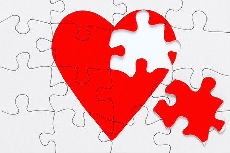 A red heart jigsaw puzzle with a piece on the side, good image for a broken heart, love, romance and Valentine themes.