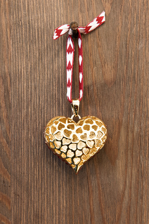 golden heart: A gold heart ornament hanging by red ribbon on a rusty nail against a rustic wooden background.