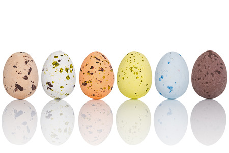 Six candy coated chocolate Easter eggs in a line, isolated on white with clipping path. photo