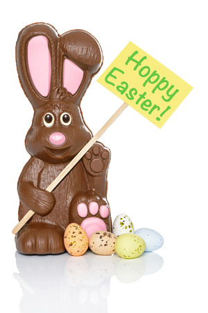 Chocolate bunny holding a sign that says Hoppy Easter, with some candy eggs at his feet. Isolated on a white background. photo