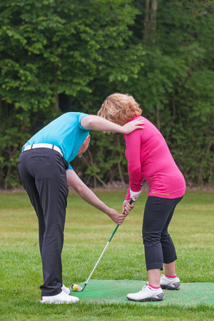 instructions: A lady golfer being taught to play golf by a Pro on a practise driving range. Stock Photo