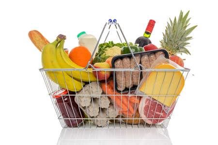 alimentacion equilibrada: Alambre cesta llena de comestibles incluidas las frutas frescas, verduras, leche, vino, carne y productos l�cteos. Aislado en un fondo blanco. Foto de archivo