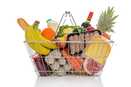 Wire shopping basket full of groceries including fresh fruit, vegetables, milk, wine, meat and dairy products. Isolated on a white background. Stock Photo