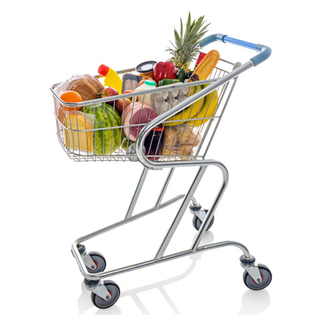 Shopping trolley full of fresh groceries isolated on a white background. photo