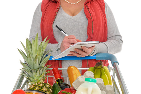 balanced budget: A woman checking her shopping list with a trolley full of fresh food, isolated on a white background.