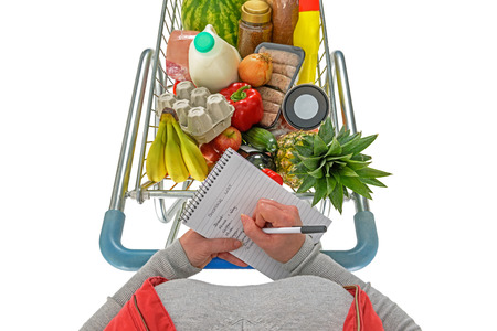 balanced budget: Overhead photo of a woman checking her shopping list with a trolley full of fresh food, isolated on a white background. Stock Photo