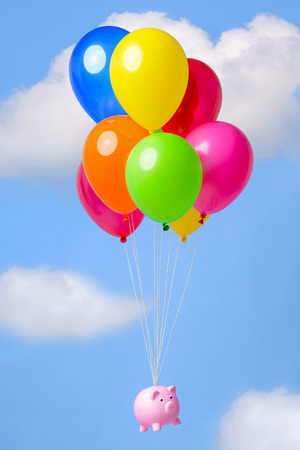 Piggy bank flying in the sky on helium ballooms, good image for finance related themes such as Inflation, Savings or Economy. photo