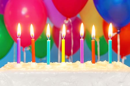 velitas de cumpleaños: Velas encendidas en un helado torta de cumpleaños blanco con globos multicolores en el fondo, copia espacio en la torta para añadir su propio mensaje.