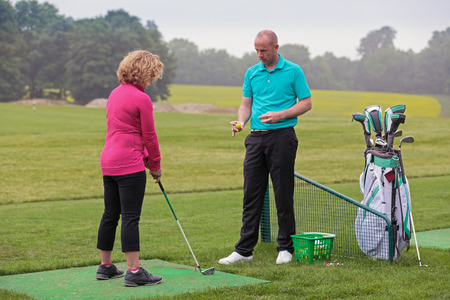 Un golfista de la señora que se enseña a jugar al golf por un profesional en un campo de práctica de la práctica. Foto de archivo