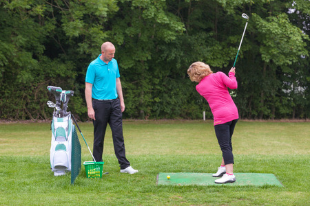 woman golf: A lady golfer being taught to play golf by a Pro on a practise driving range. Stock Photo