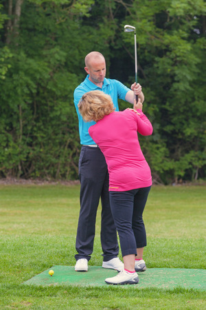 taught man: A lady golfer being taught to play golf by a Pro on a practise driving range. Stock Photo