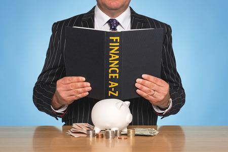 bankroll: A businessman sat at a desk reading a FINANCE A-Z book
