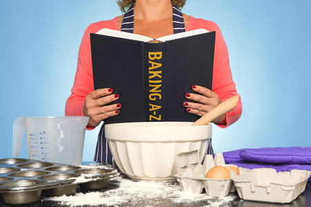 A woman standing at a kitchen worktop reading a BAKING A-Z book photo