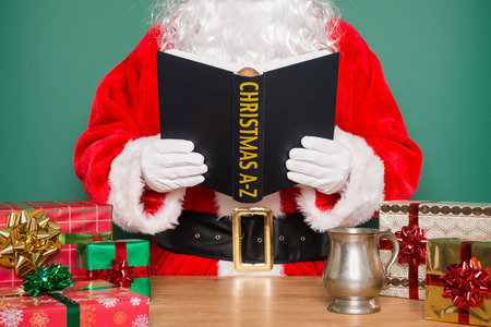 Santa Claus or Father Christmas reading a Christmas A-Z book whilst stood at his desk in the North Pole. Stock Photo